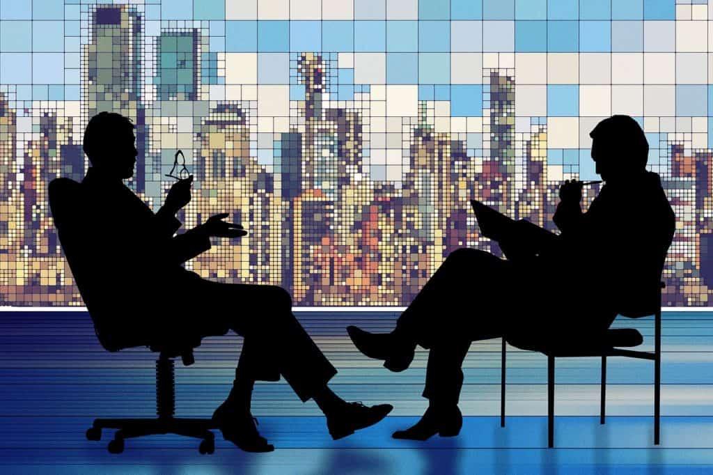 negocjacje dwóch biznesmentów w sali z widokiem na tle wierzowców