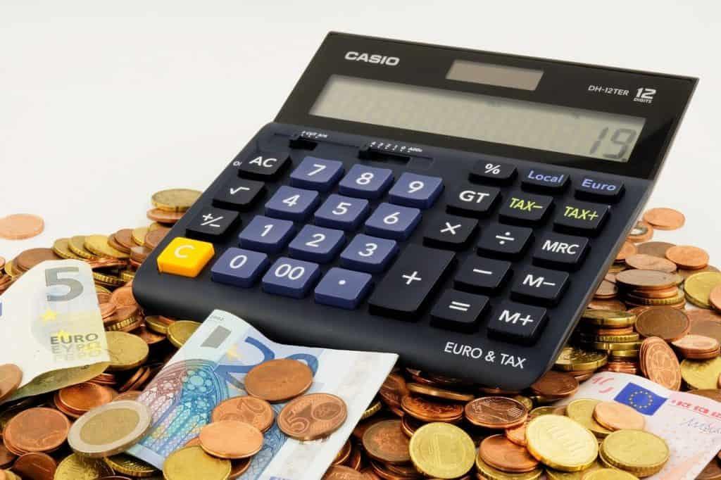 kalkulator leżący na monetach i banknotach euro
