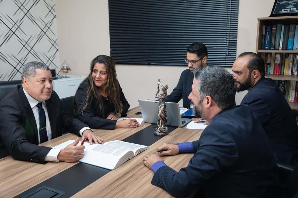 mężczyźni i kobieta siedzą i rozmawiają przy stole konferencyjnym