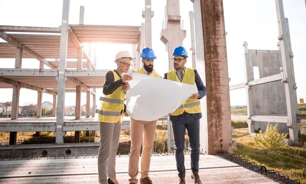 trzech mężczyzn ogląda plany budowy na tle powstającego budynku