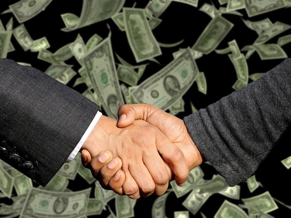 uścisk dłoni na tle spadających banknotów