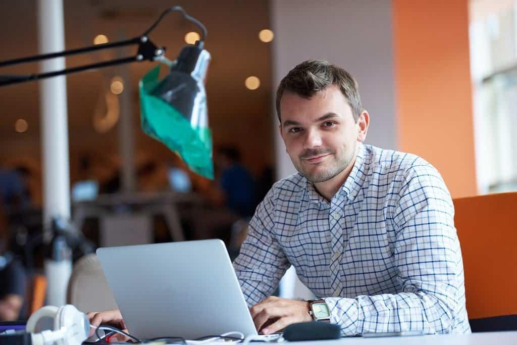 uśmiechnięty mężczyzna pracuje na laptopie przy lapmie w biurze