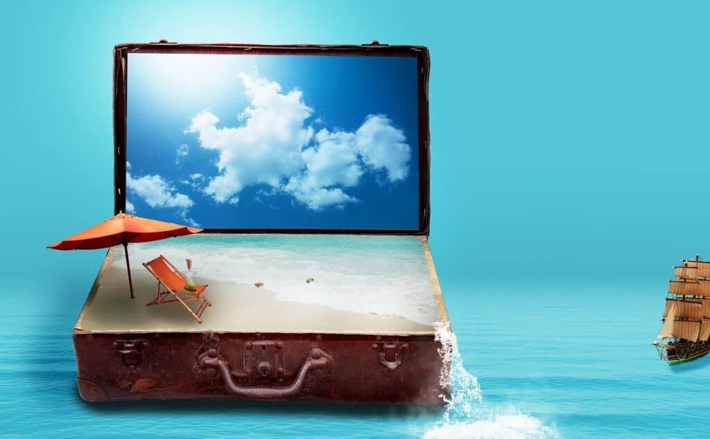 otwarta walizka wakacyjna z piaskiem, parasolem i kocem plażowym na tle błękitnego nieba