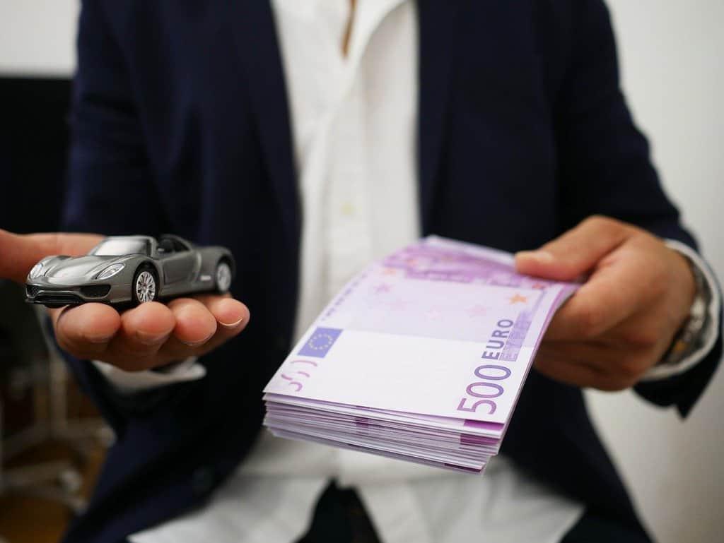 osoba w białej koszuli i czarnej marynerce trzymająca w jednej dłoni banknoty a w drugiej mały samochód