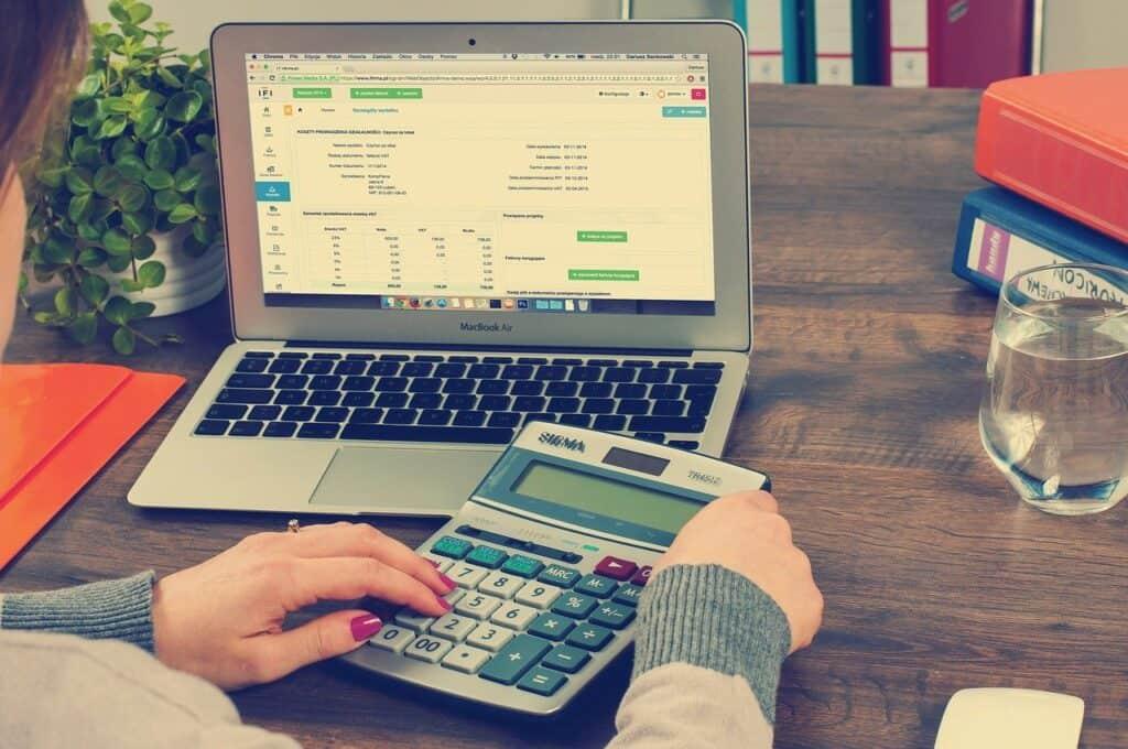 kobieta siedząca przy stole z laptopem i kalkulatorem