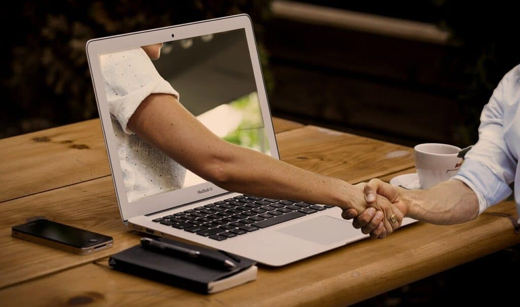 wirtualny uścisk dłoni pomiędzy osobą siedzacą przy biurku, a osobą wychodzącą z laptopa