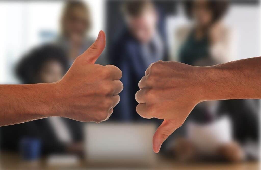 dwie dłonie wskazujące kciuk w górę i w dół