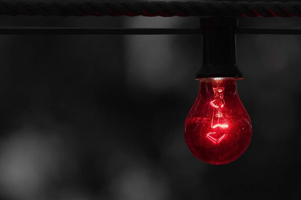 święcąca na czerwona żarówka na czarnym tle