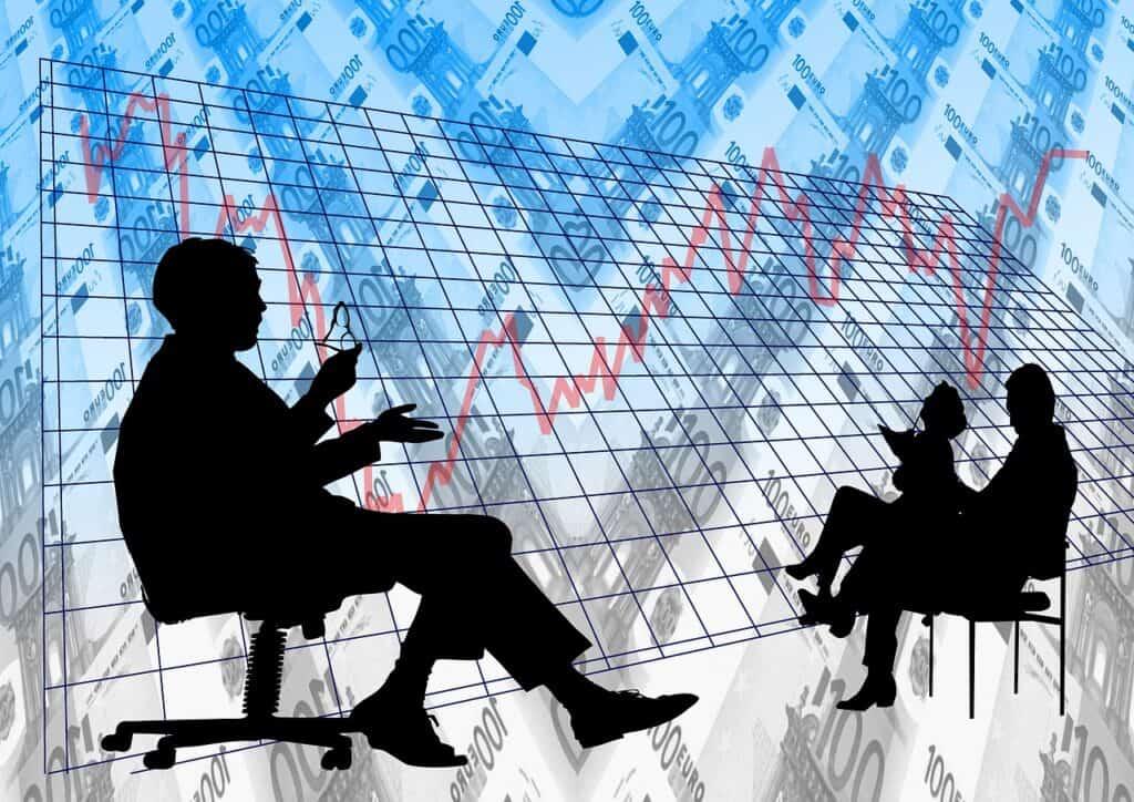 dwie postacie dyskutujące na tle wykresów finansowych