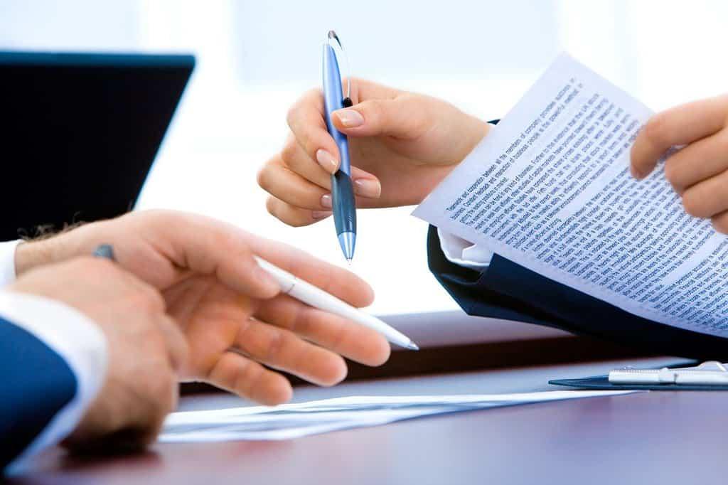 umowa podpisywana przy stole przez dwie osoby
