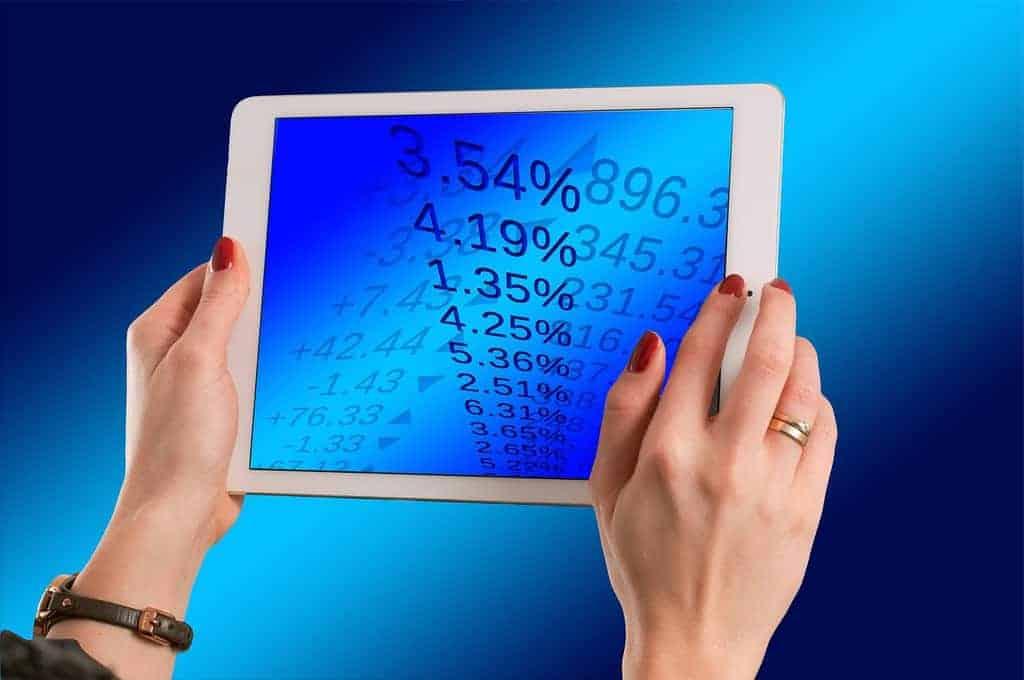tablet z danymi liczbowymi trzymany w kobiecych dłoniach