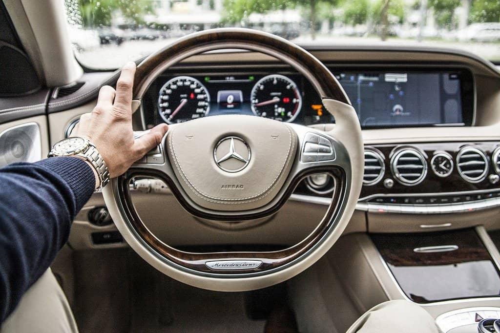 mężczyzna trzymający kierownicę w eleganckim samochodzie