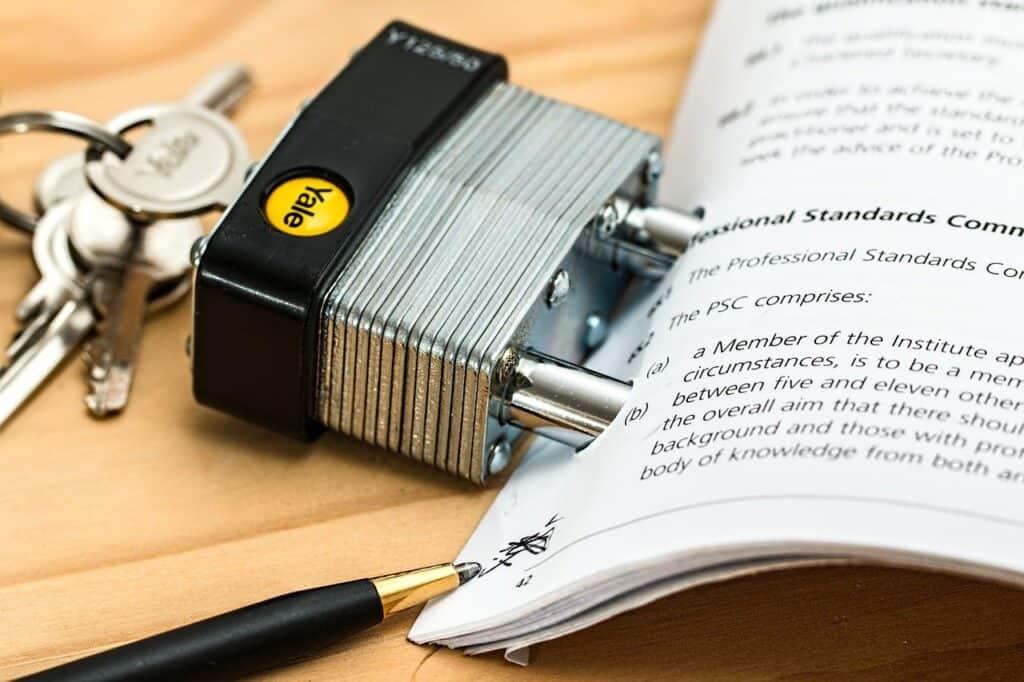 kłodka założona na dokumentach leżących na stole