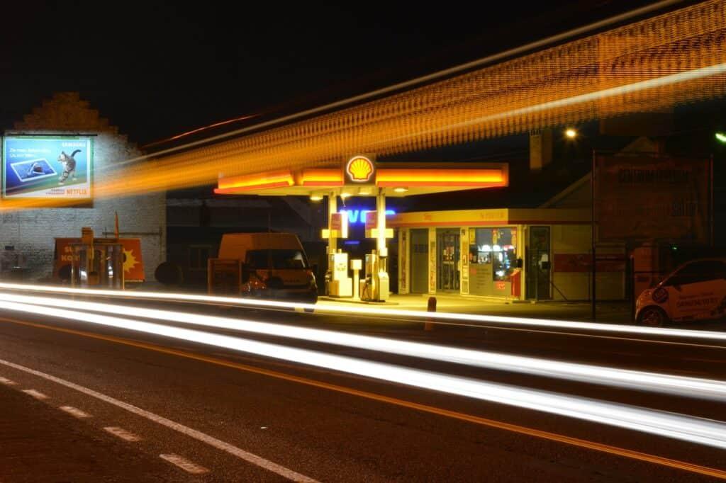 światła stacji benzynowej nocą z perspektywy pędzącego samochodu