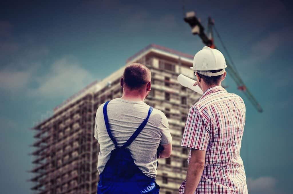 dwóch mężczyzn na budowie spogląda na powstający wierzowiec