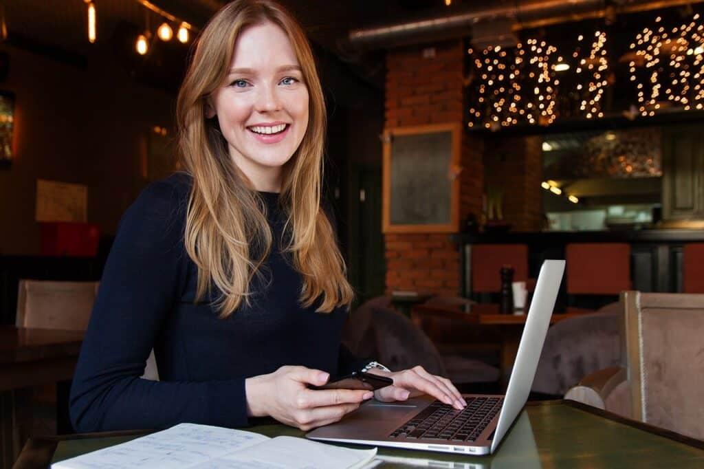 młoda uśmiechnieta kobieta z telefonem siedząca przy laptopie