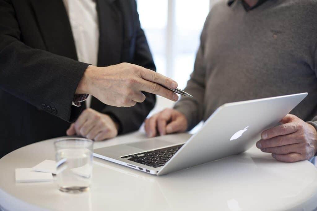 dwie elegancko ubrane osoby rozmawiają przy stoliku na ktorym stoi laptop