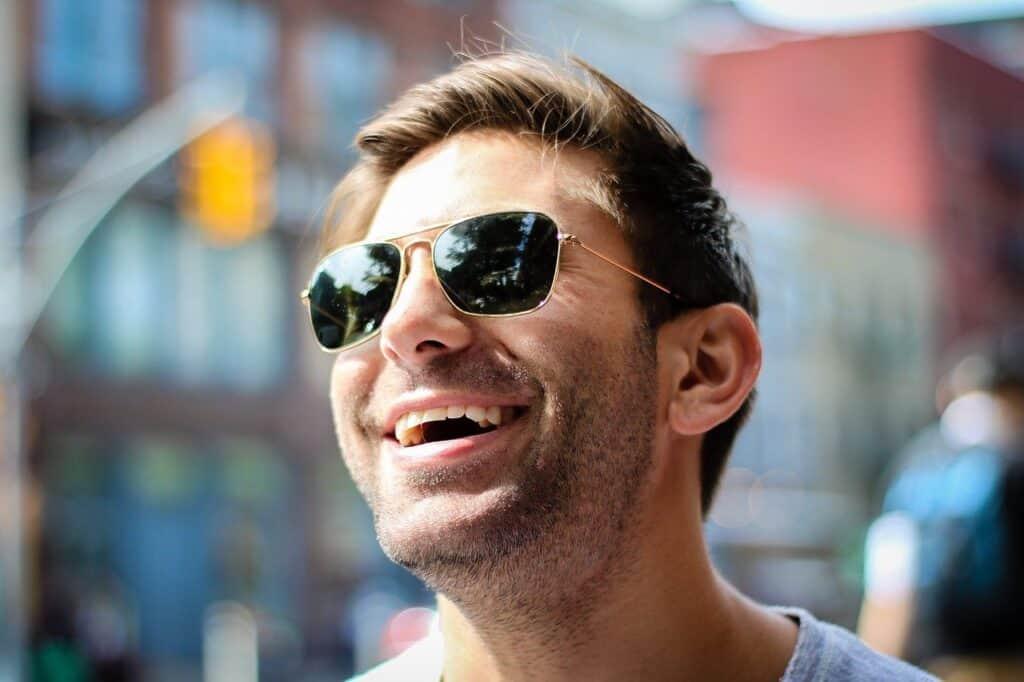 uśmiechnięty ężczyzna w kolularach przeciwsłonecznych