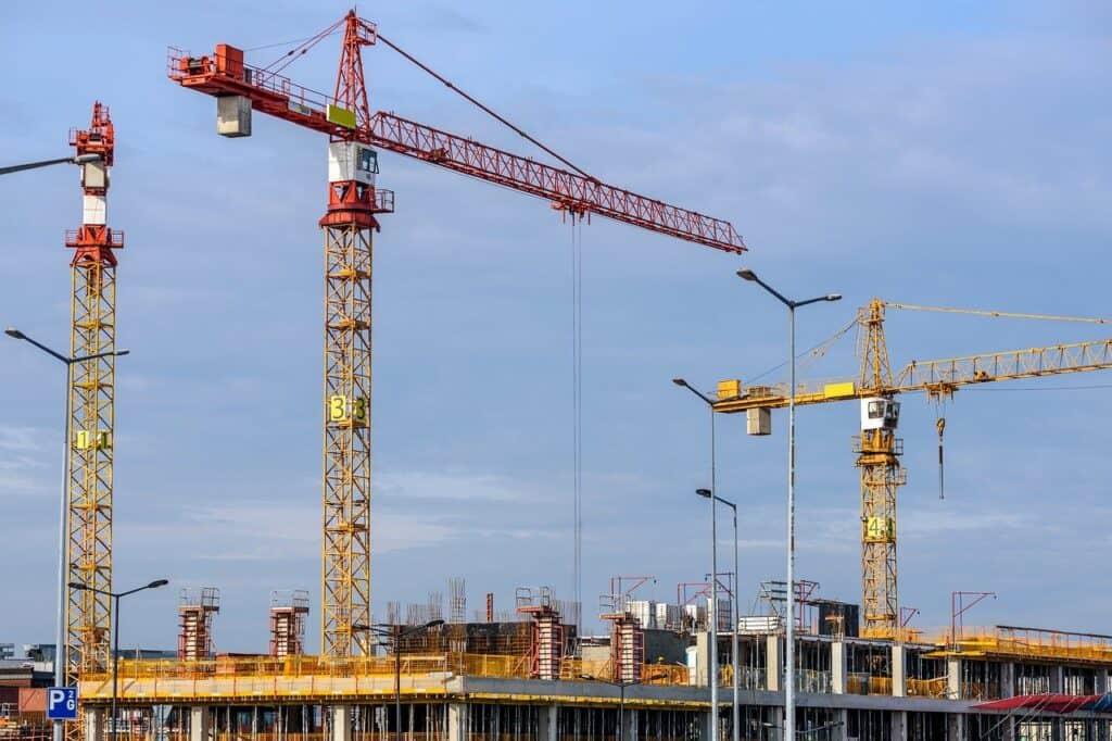 duże dźwigi pracujące na budowie