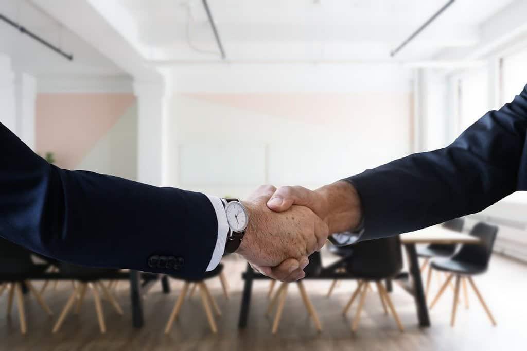 uścisk dłoni pomiędzy dwoma mężczyznami w sali konferencyjnej