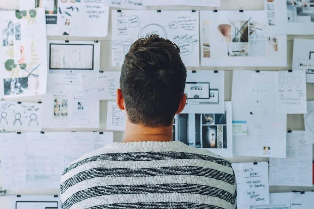 mężczyzna patrzący na tablicę z projektami