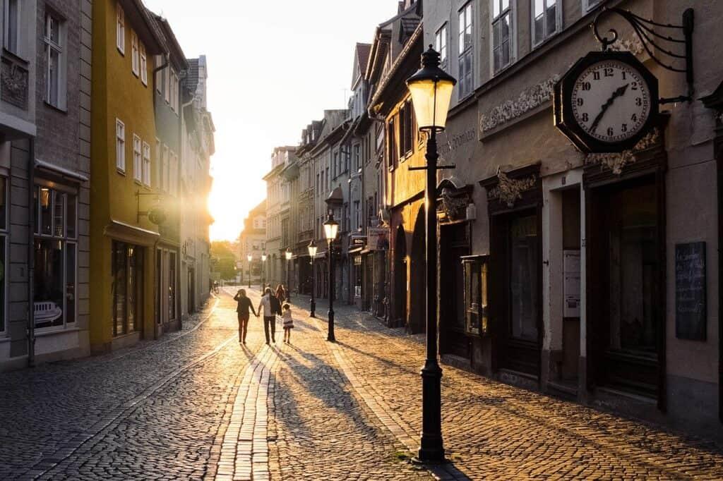 ludzie spacerujący uliczkami miasta o zachodzie słońca