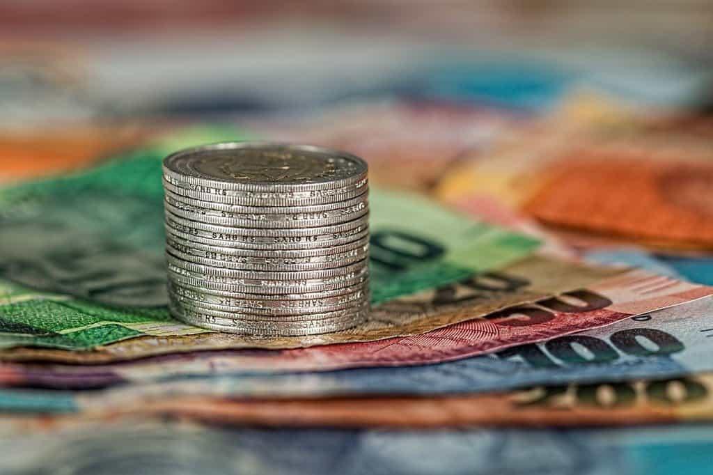 stos monet ułożonych na banknotach