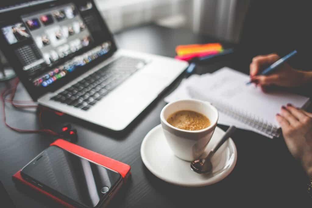 filiżanka kawy stojąca przed otwartym laptotem i dokumentami