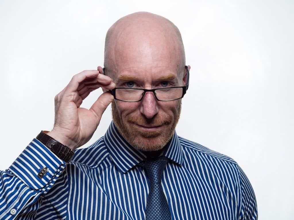 mężczyzna w koszuli i krawiacie spoglądający znad okularów
