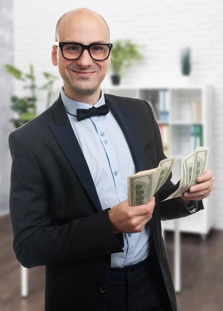 elegancko ubrany mężczyna w okolarach trzymający banknoty