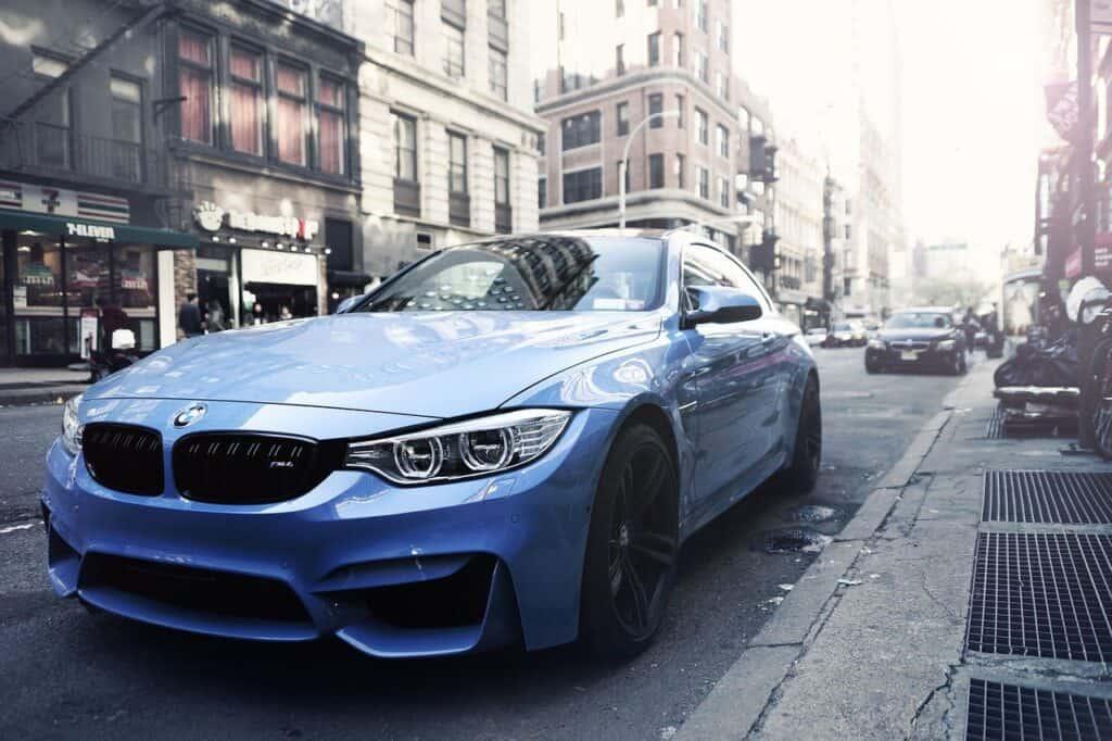 luksusowy, niebieski samochód zaparkowany przy chodniku w mieście