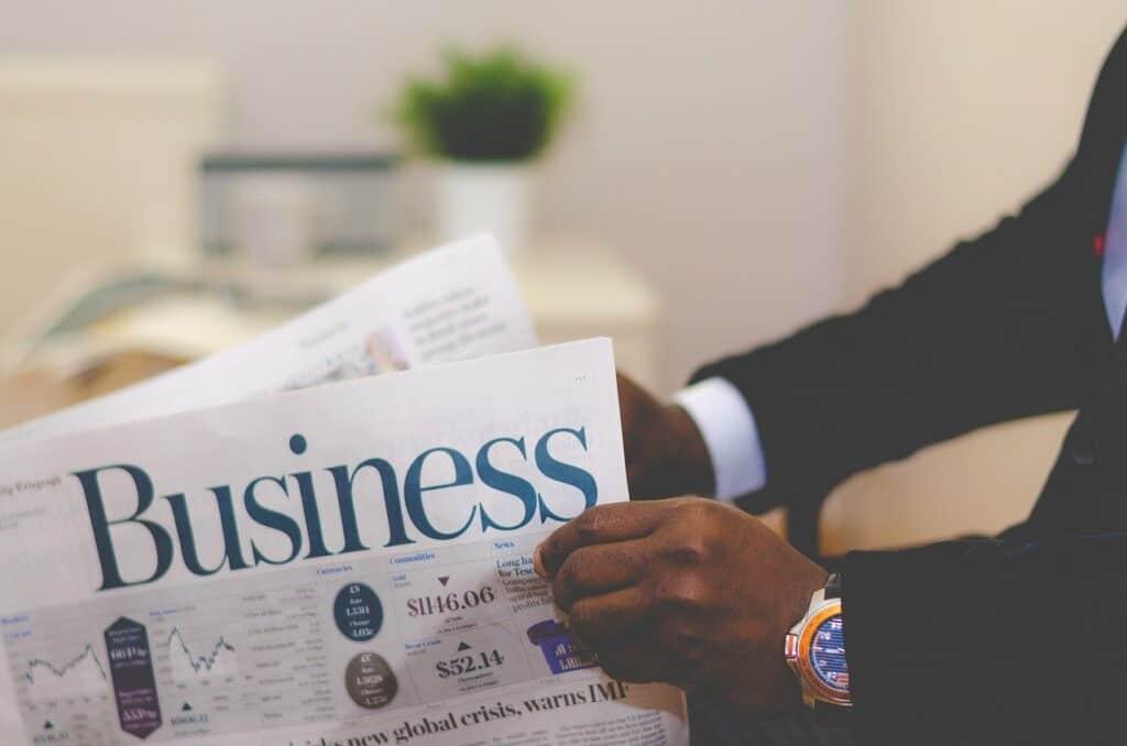 mężczyzna w garniturze czytający gazetę biznesową