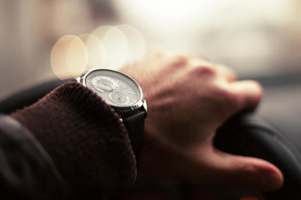 męska dłoń z eleganckim zegarkiem trzymająca kierownicę