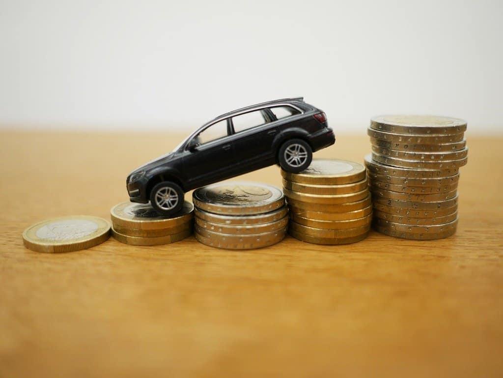 miniatura samochodu ustawiana na stosach monet