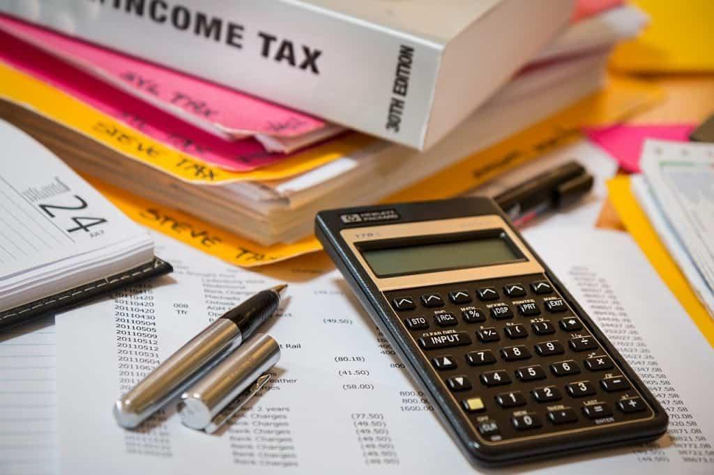pióro, kalkular i róóżne dokumenty podatkowe leżące na stole