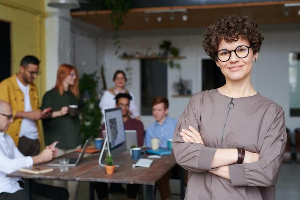 Uśmiechnięta kobieta na tle grupy osób przy biurku z komputerem