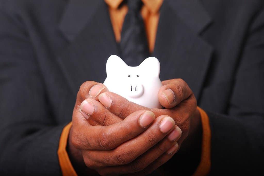 mężczyzna w garniturze trzymający w dłoniach świnkę-skarbonkę
