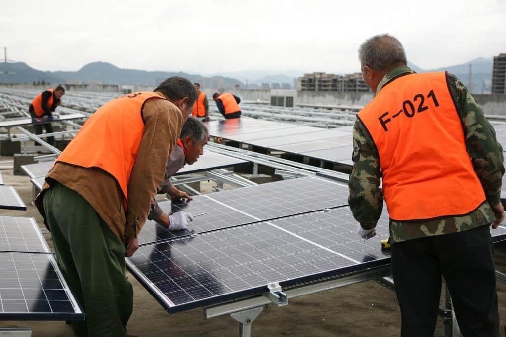 mężczyźni montujący panele fotowoltaiczne
