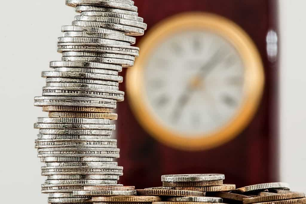 stos monet na tle zegara wiszącego na ścianie