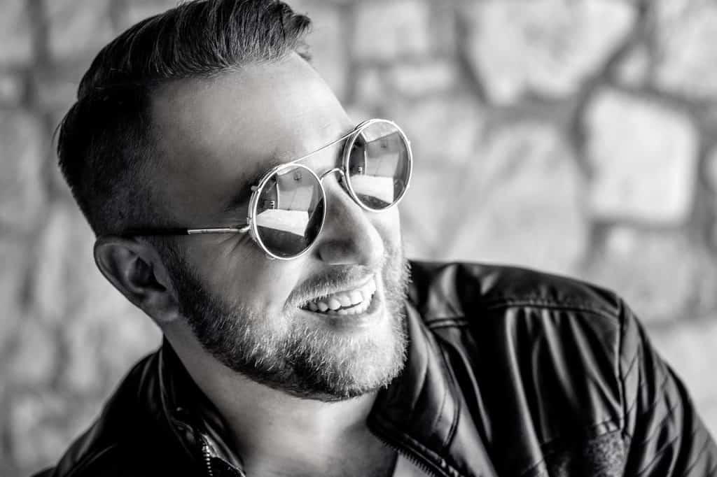 uśmiechnięty młody mężczyzna w okoularach przeciwsłonecznych